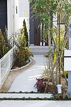 玄関へ続くアプローチを植栽で彩り、緑豊かな空間に。(施工例)