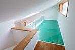 A号棟ロフト  階段で登れるロフト。増えがちな季節の衣類や本、趣味の道具などもすっきりと片付きそうですね。デザイン性のあるマス目の床となっております。