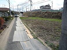 北側からの前面道路と右宅地