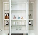 洗面化粧台の鏡は、メイクや髭剃りに便利な三面鏡タイプ。鏡の裏側は収納スペースとして利用でき、小物などの保管に便利な棚も付いています。
