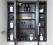 洗面化粧台の鏡は、メイクや髭剃りに便利な三面鏡タイプ。開いて合わせ鏡としても使用できます。鏡の裏側は収納スペースとして利用でき、小物などの保管に便利な棚も付いています。