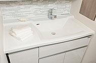 洗面は片側に寄せて、ワークスペースを確保。つぎめがない一体型の化粧台は、美しくお手入れも簡単です。
