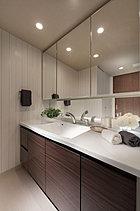 家族が一緒に室内にいてもスムーズに動けるゆとりを確保した洗面室には、ワイドなカウンターと三面鏡を備えた洗面化粧台を。壁面のリネン庫など、収納にも配慮し、空間をすっきりと。リラクゼーション空間としてのしつらえにこだわりました。