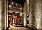 ときめきと開放を感じさせる二層吹抜の天井。木調の温もりある質感を豊かに表現しつつも、モダンであることに徹したインテリア。それぞれのプライベートへの境界でありながら、非日常的な空間性を湛えたエントランスホールが、訪れる人を迎えます。