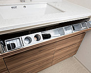 洗面ボウルの下がパタッと開き、小物の整理に便利な収納です。また、収納するものに合わせて仕切りプレートが移動できます。