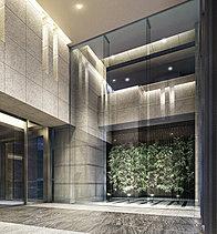 リゾートホテルを彷彿とさせる2層吹き抜けのエントランスホール。縦方向への広がりを意識するとともに、天井までガラスを貼ることで、開放感を演出しています。
