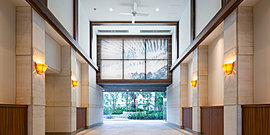 アートが出迎える住まいの入口へ。エントランスから続く開放的な吹抜の迎賓空間。壁に並んだアートや天井に設けた飾り壁、その奥に配した緑豊かな中庭がオーナーを住まいへと誘います。