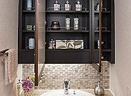 鏡の上下に框を配したスタイリッシュな洗面化粧台は、鏡の裏に収納スペースを確保しました。コンセントやティッシュバーなど、機能性にも配慮しています。