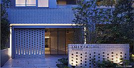 透かし積みブロックから漏れる柔らかい光が迎えるエントランス。建物に一歩入ると、ファブリックガラスとラウンドタイルの立体感あるエントランスホールが住まいへと導きます。
