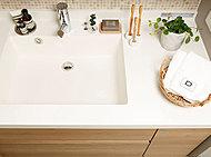 洗面時間を気持ちよく。洗面ボウルをサイドに寄せて配置。ボウルの横にまとまったスペースがあるので、小物や化粧品などの置場としても使えます。