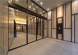 エントランスを人った先に広がるのが、「エントランスホール」。御影石の床が上質感を演出。壁には、「磁器質タイル」や「ローマタイル」、「大理石」、「アルミ」のラインなど様々な素材で、幾何学的な面構成をデザイン。
