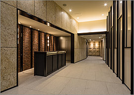 エントランスホールには、コンシェルジュカウンターを設置。住まう方の毎日に様々なサービスを提供する。御影石の高級感漂う床に映える石のカウンターを設え、壁にはレンガ調のタイルやタペストリーを配した。