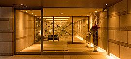 光と建築の融合を安息の空間へと昇華させたエントランスホールの佇まい。エントランスから連続する石貼りの壁は建物の品格を迎賓の間に映し、まばゆい光や咲き誇る花々をモチーフにしたアートガラスがやすらぎの時間を醸成する。