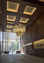 共用空間にいながら開放感あふれる、二層吹き抜けのエントランスホール。エントランスラウンジに向け、段階的に天井を高く設計してより深い居心地を創出。またコンシェルジュカウンターにも、一貫した迎賓の精神を込めています。