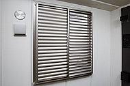 共用廊下に面した居室の窓には可動ルーバー付きの面格子を設置。プライバシーに配慮しながら光や風を取り込めます。