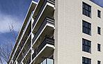 外観には落ち着いたアースカラーのタイルを使用し、モダンで端正な佇まいに。バルコニーはガラス手摺とデザインルーバーをランダムに配置。採光性と通風に加え建物全体に印象的なアクセントを生み、住戸ごとに異なる個性を与えます。
