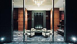 赤の大理石造りの列柱が並び立つ天井高採光約5.1mの2層吹抜けのグランドエントランスホールへ。そこには、ホテルのトップスイートも手がける「B&Bitalia」のファニチャーが並び、格調高いロビー空間を演出する。