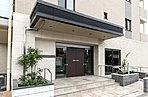 洗練された暮らしのシーンを予感させるエントランスアプローチの床面は、さまざまな色彩のタイルを組み合わせることで邸宅感を創出。さらに、ダークカラーのキャノビーから壁面、扉、植栽の細部にまで確かなセンスが息づいており、住まう方とゲストを優しくエスコートします。