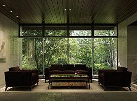 自然との融和から生まれた、上質なくつろぎ。エントランスホールの中程、窓外に緑の小径を眺める位置にラウンジコーナーを配しています。落ち着いた色調のコーディネイトに包まれて過ごす、憩いと語らいのスペース。