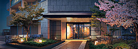 エントランスアプローチには、春と秋に風情を添えるソメイヨシノとイロハモミジの彩り。短冊型に御影石を敷いた延段を模した床、さらに風格を高める石垣や和のテイストを加える縦格子、そして庇など趣向を凝らした空間デザインです。