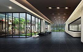 グランドエントランスから建物内へ足を踏み入れると、そこは落ち着いた雰囲気の中に明るい光が差し込む「エントランスホール」。 開放感を広げるガラスサッシを介して、中庭の緑との一体感をデザイン。