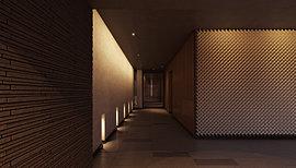 エントランス(前庭)からエントランスホール(奥の間)へと誘う中間領域を、「通り庭」と名付けました。足元を照らす小窓の明かりを動線に、ツヤのある漆喰風の壁と石畳のリズムを現代的なデザインに昇華した床タイルの貼り分け。