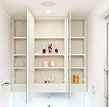 化粧品や小物などの収納に便利な大型三面鏡を設置。洗面化粧台廻りを美しく保つことができます。