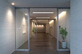 エントランスからホールに至るまでの壁面は、アイボリー系の大判タイルで統一感を演出し、外の世界からプライベート空間への連続性を表現しています。