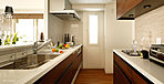 リビング・ダイニングに開放感を生む対面カウンターキッチン。木目調の面材を採用して、デザイン性を高めています。