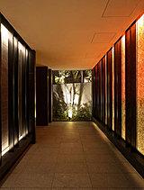 間接照明が和紙を艶やかに照らす優美な光壁と、シックなタイルとのコントラストが美しい迎賓空間。日本の伝統的な建物内部から望む庭園の借景をヒントに美意識を刺激する和モダンの世界観を表現しました。