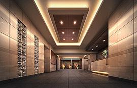 落ち着きと重厚感のある意匠が、訪れる人々を包みこむエントランスホールは、ホテルのロビーのような静謐で洗練された空気感に満ちています。正面には潤いと癒やしの風景を創出する坪庭を設置。柔らかな照明の光によって、さらに高級感とステイタス感を高めました。
