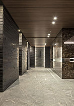 エントランスホールの隣には、大切なゲストを迎える空間としての、広やかなラウンジを設けました。光の列柱を思わせる照明が、重厚感のある空間に華やぎを与え、洗練されたもてなしの時を演出します。