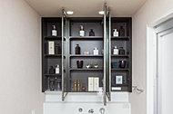 洗面化粧台の鏡裏に収納スペースを確保。シェーバーなどを充電しながらしまえるコンセントも設けました。