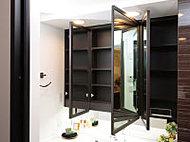 鏡を木製フレームで囲い、洗面室をシックな印象に。鏡の裏側には収納スペースを設けました。