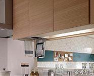 吊戸棚の下段には小物収納、ラップ収納、ペーパーホルダーを設置。底面のラックを下ろすと、タブレットパソコンや本などのレシピを置くことができます