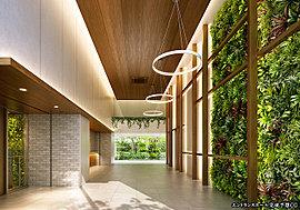 天井高約4.5mの開放感あふれる「エントランスホール」。正面には、床から天井までの壁面緑化を設え、室内にいながら緑を大胆に感じられる空間を創出します。白と木目を基調としたミニマルデザインは、シンプルでありながらぬくもりの空間を演出。