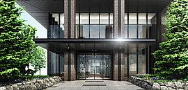 グランドエントランスは2層吹抜・ガラス張りの光に映えるデザインに仕上げました。縦に伸びる石貼りの柱と横に広がるモノトーンの庇がコントラストとなり、開放感と重厚感のある表情豊かな佇まいを創り出しています。