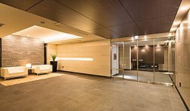 邸宅にふさわしい品格ある木目調のエントランスドアを抜けると、重厚感あるブラックの床とホワイトの壁を配した、シックで落ち着きある設えのワイドなエントランスホールが現れます。※平成27年3月撮影。