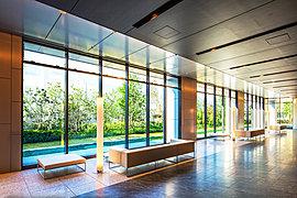 グランドエントランスから一歩足を踏み入れると、高級感あふれるグランドロビーが迎えます。ここは格調高い御影石貼の床や木目調のデザインウォールを採用した、迎賓空間。やわらかな光の間接照明が連続するデザインで奥行きを表現。
