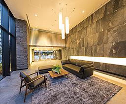 温かみのある木調のルーバーと迫力あるガラススクリーンが、ゆとりある開放感を創る2層吹抜けのメインエントランスホール。