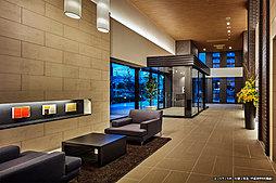 二層吹抜の圧倒的な開放感。そして、外観と統一されたモノトーンタイルの床や壁と温もりのある木目調の天井。「シティハウス八王子北野ステーションコート」のエントランスは、落ち着きと安らぎが漂う上質なインテリアで仕上げられています。