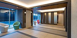 外部のゲートの趣きをエントランスホールの天井から壁、そして床へとつなげてデザイン。ガラス鏡のように見立て、天井や床を連続する空間として広がり感を演出しています。