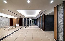 エントランスホールには、迎賓の印象とともに品格を創出。アクセントとなる壁面には、色と仕上げの異なる天然石を組み合わせ、そこに木調の温かみを加えたルーバーを配することで、落ち着きと高級感を演出しました。