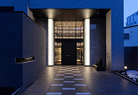 上質で品格のある迎賓空間。ホテルのロビーを思わせるエントランスホールは、高級感溢れる吹き抜けを有するデザイン。2層吹き抜けのガラスウォールと照明ウォールボックスが、ファサードにインパクトを与え、周りには天然御影石などを配しています。