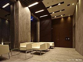 エントランスホールは、約3.9メートルの天井高で開放感を演出。床と壁に磁器質タイルを、壁と天井の一部にアクセントとしてアルミルーバーを採用しています。大きな開口部からは自然光が射し込み、夜はダウンライトが空間を優しく包みます。