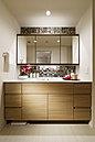 ワイドなミラーやタイル、木調素材が上質さを奏でるパウダールーム。