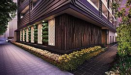 愛宕上杉通からエントランスに伸びたタイル。そこに、基壇部に施されたフラットプレートルーバーを通してホールの光があふれ、日本的な風情を醸し出す迎賓のアプローチを演出。