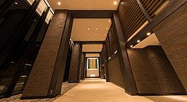 厳選された素材の質感を引き立てる光の演出と、モダンな設計思想の息づく開放感あふれる2層吹抜けが迎えるエントランスホール。印象的なゲート型の柱・梁の奥には、シンメトリー構成のオリジナルアートを飾り、アーティスティックな感性が息づく空間を創出。