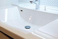 洗面台にはスクエアで継ぎ目がなく美しいデザインの人造大理石ボウルを採用。片寄せ配置で、着替えも置ける仕様です。