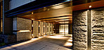 外界の光景にふれる、和みのラウンジ。天井までのびたガラスの開口部は、光溢れる外界の景色を映すおおらかな空間を演出。大理石を門型に構成した格式あるシンメトリーな空間に、木調の素材感が、洗練された温かさを醸し出します。